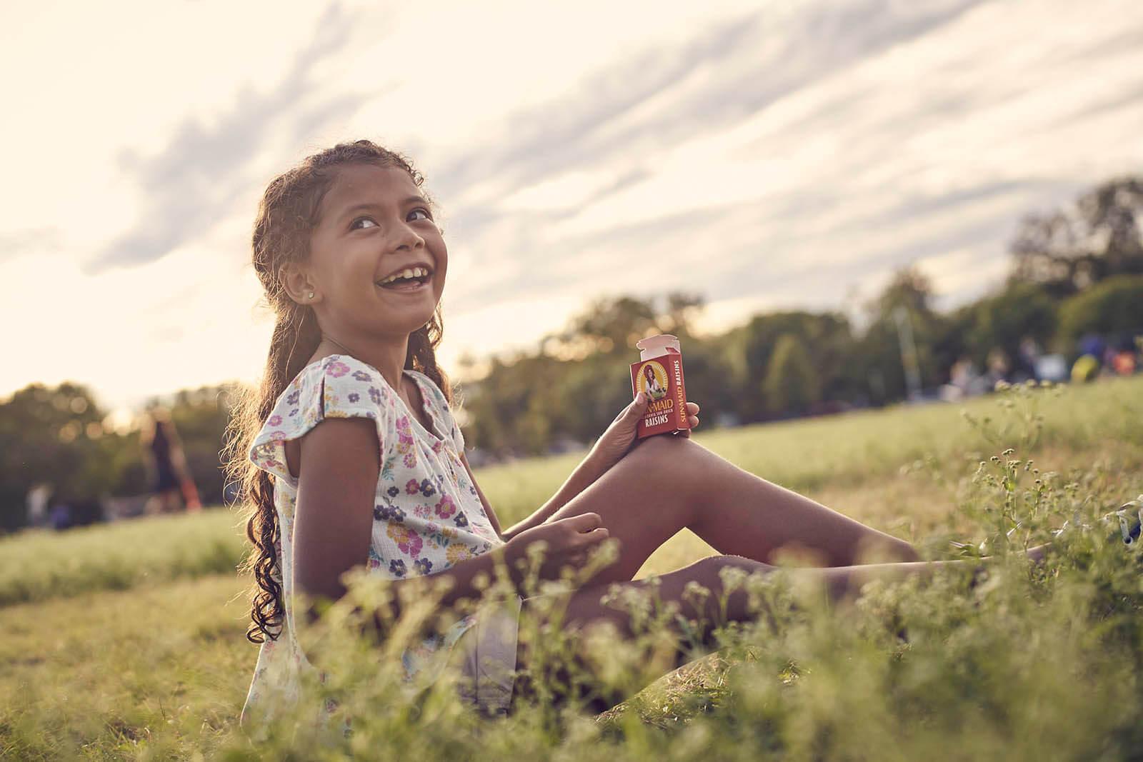 Child sitting in a field eating Sun-Maid raisins